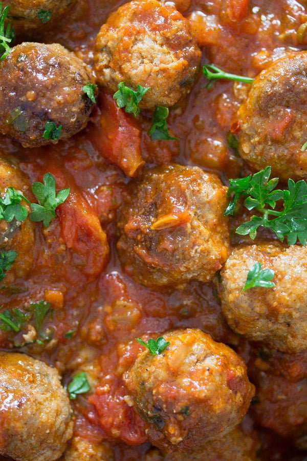 close up of meatballs in sauce with parsley