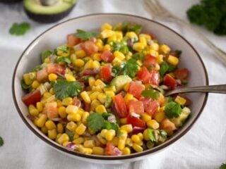 corn tomato salsa in a white bowl with a spoon