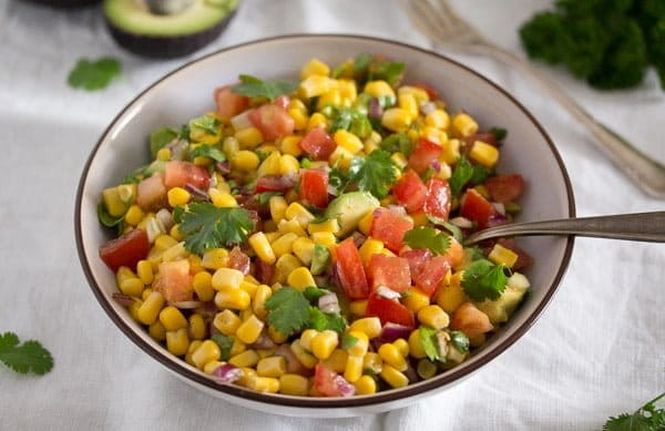 corn tomato salsa in a white bowl with a spoon