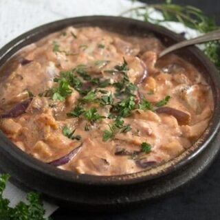 persian eggplant dip in a brown bowl with a spoon