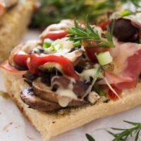 polish zapiekanka topped with mushrooms and cheese close up