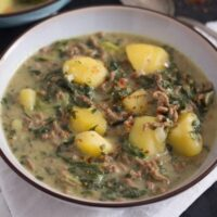 beef and potato curry cooked with spinach and yogurt served in a bowl