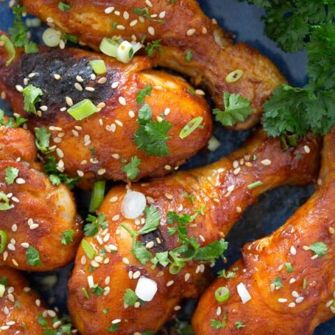 baked drumsticks with honey and soy sauce on a blue plate.