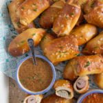 pretzel pigs in a blanket served on a wooden serving tray