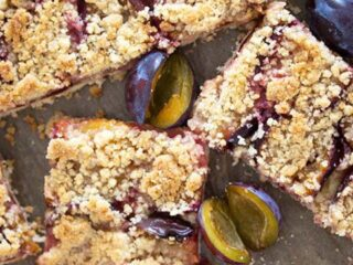 slices of zwetschgenkuchen and small plums on a baking tray