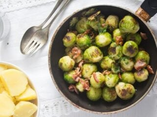 brussels sprouts german-style in a small pan with a side of boiled potatoes