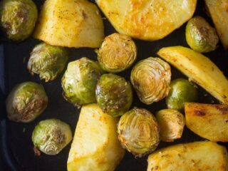 roasted potatoes and brussel sprouts on a black baking tray