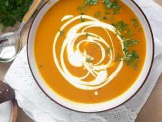curried sweet potato pumpkin soup in a bowl with coconut cream