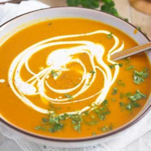 pumpkin and sweet potato soup in a small bowl garnished with parsley