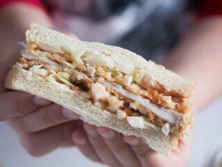 tonkatsu sandwich being held by a boy's hands