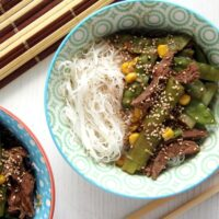 bowl with noodles, meat and vegetables overhead picture.