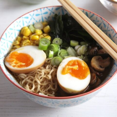 ramen soup with soy sauce eggs and noodles in a bowl