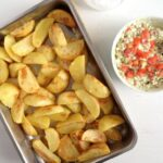 baked potatoes in a roasting tin served with cottage cheese dip