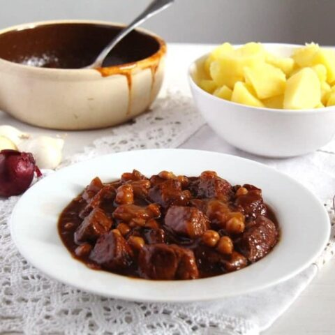 spanish stew with pork served with potatoes