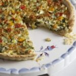 quiche with a slice missing on a vintage platter with blue flowers.