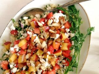 fruit quinoa salad with herbs on a platter with a spoon