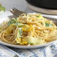 plate with yellow pasta with cream and zucchini