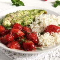 chicken with strawberries and rice being served on a white plate