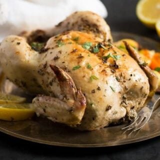 greek baked chicken with a halved lemon in the back
