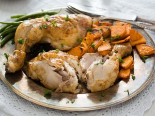 roasted chicken leg quarters served with sweet potatoes on a vintage plate