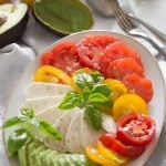 italian insalata tricolore with tomatoes and avocado on platter with a spoon
