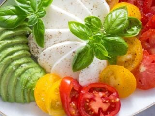 tomato avocado mozzarella salad sprinkled with pepper and topped with basil leaves
