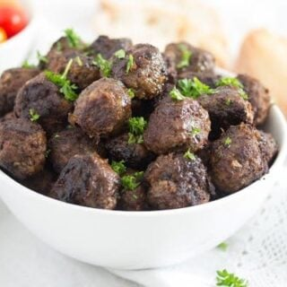 turkish beef meatballs in a white bowl served with bread and tomatoes