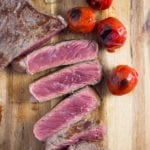 italian steak sliced on a wooden board with tomatoes