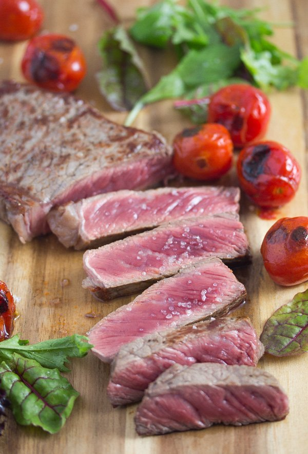 Medium rare beef tagliata recipe or Italian sliced steak served with pan fried tomatoes.