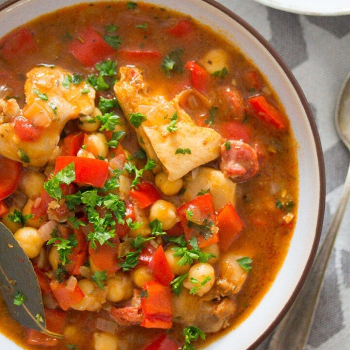 bowl of spanish chicken and chorizo stew with peppers and chickpeas