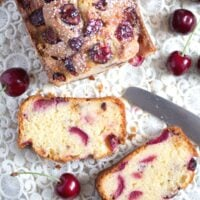 cherry loaf cake sliced on a vintage cloth with a knife and fresh fruit around it.