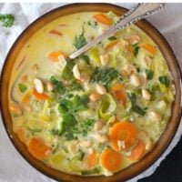 close up of a bowl of peanut milk soup with carrots and leeks with a spoon in it.