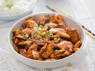 gochujang chicken breast strips sprinkled with sesame in a bowl