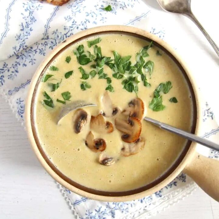 healthy mushroom soup without cream topped with parsley in a small clay pot.