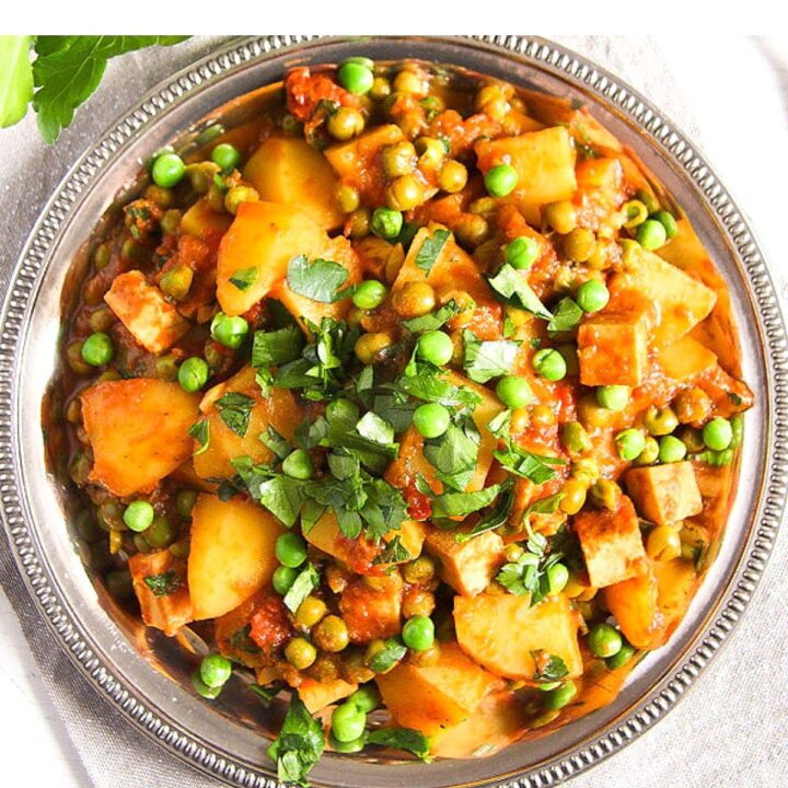 vegan tofu potato curry sprinkled with peas and parsley overhead picture