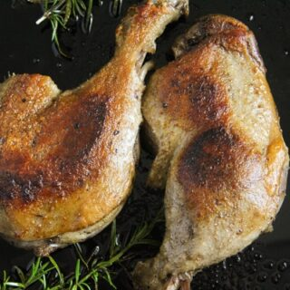 fried duck leg confit in a pan with potatoes
