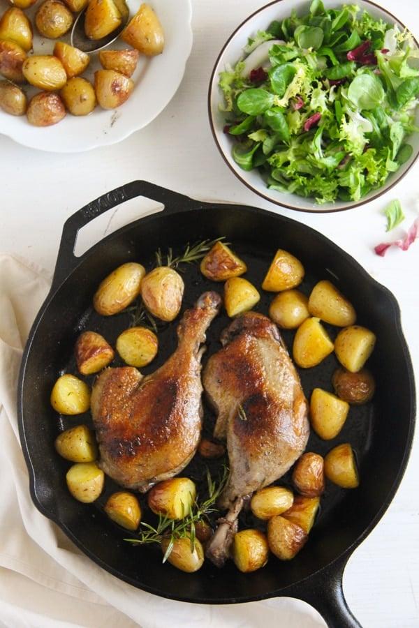 confit de canard in a cast iron pan with potatoes