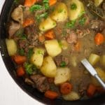 red pot full of potatoes, meat and carrots