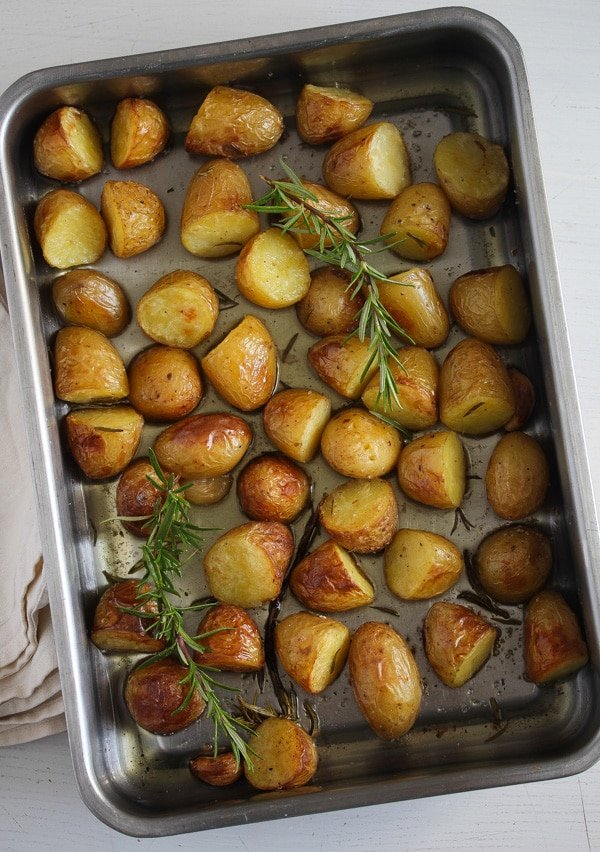 potato confit with rosemary with goose fat in a roasting pan