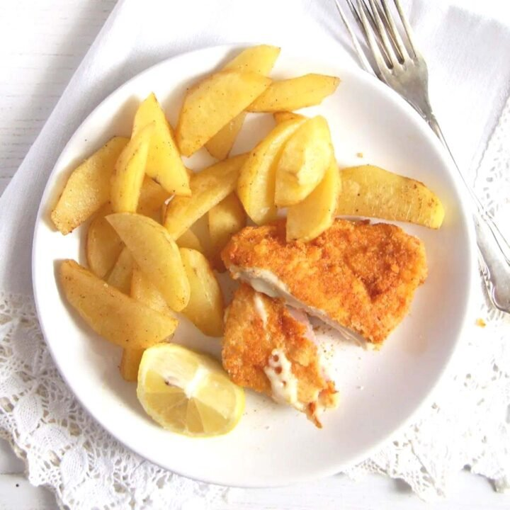 overhead image of a cut cordon bleu schnitzel served with potatoes.