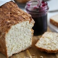 sliced oat bread without yeast with a jar of jam behind.