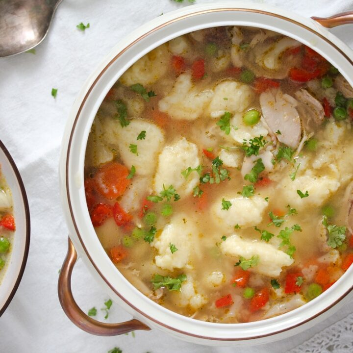 chicken soup with dumplings and veggies in a serving bowl