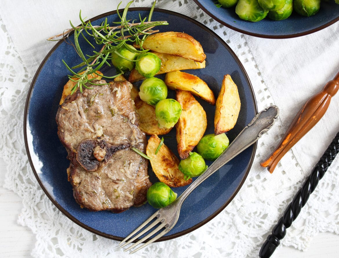 roasted lamb on a blue plate with potatoes, rosemary and brussels sprouts