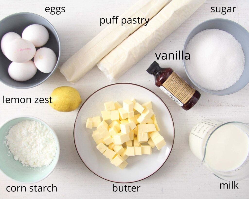 eggs, puff pastry rolls, sugar, butter, milk and cornstarch in bowls