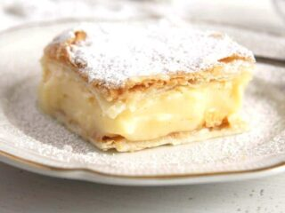 cremeschnitte piece sprinkled with icing sugar on a plate