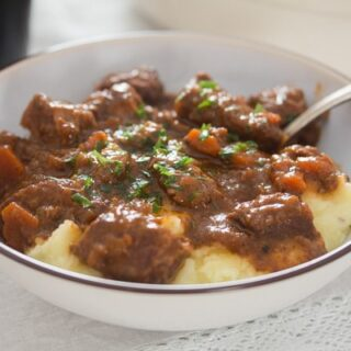 irish beef stew in a bowl with mashed potatoes