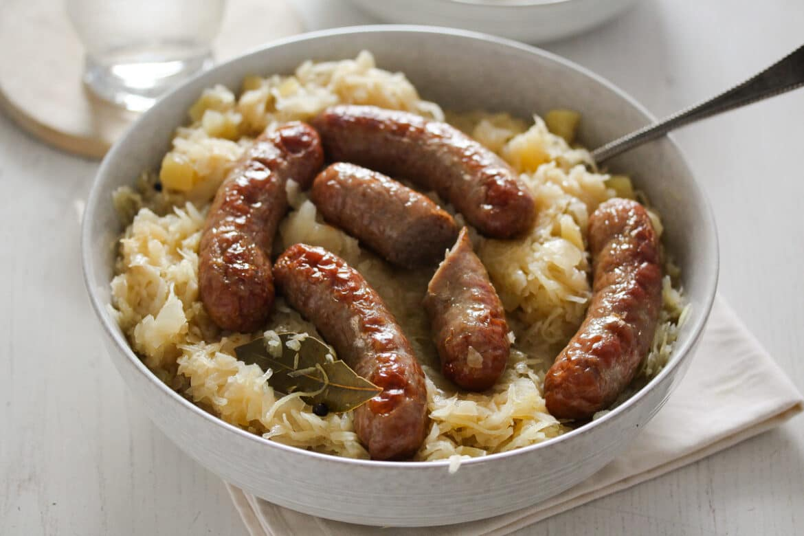 brats and sauerkraut in a white bowl