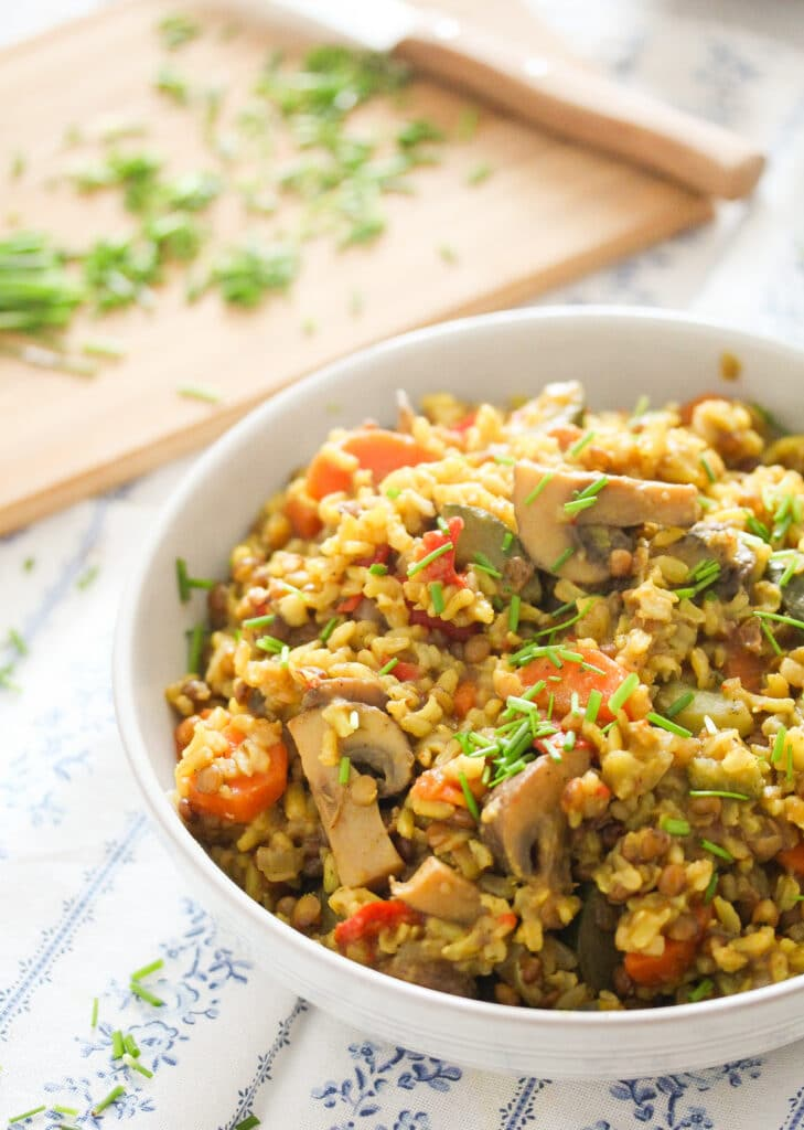 lentils and rice in a white bowl with chives