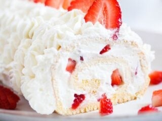 close up of sliced cream roll with strawberries