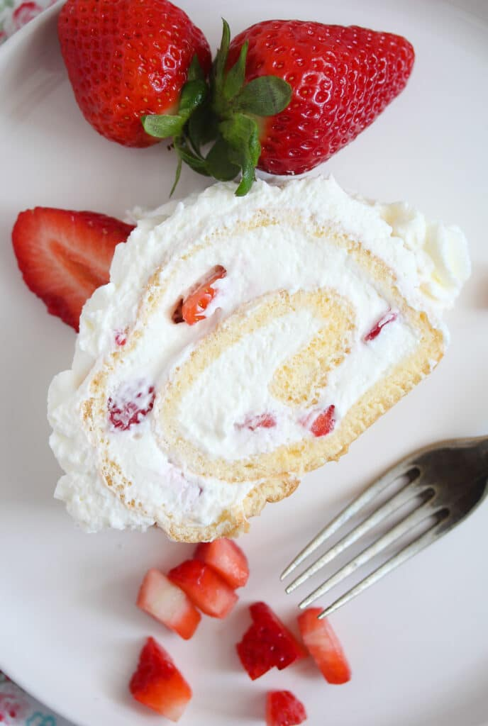 slice of cream cake with berries on a white plate with a fork